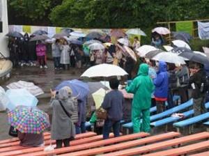 ▲猛雨の中で舞台を見つめる参加者たち