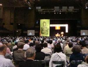 ▲全体会場で「記念講演」を聞く参加者たち